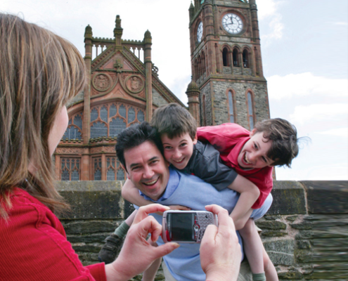 couple with son outside the guildhall derry on destination derry